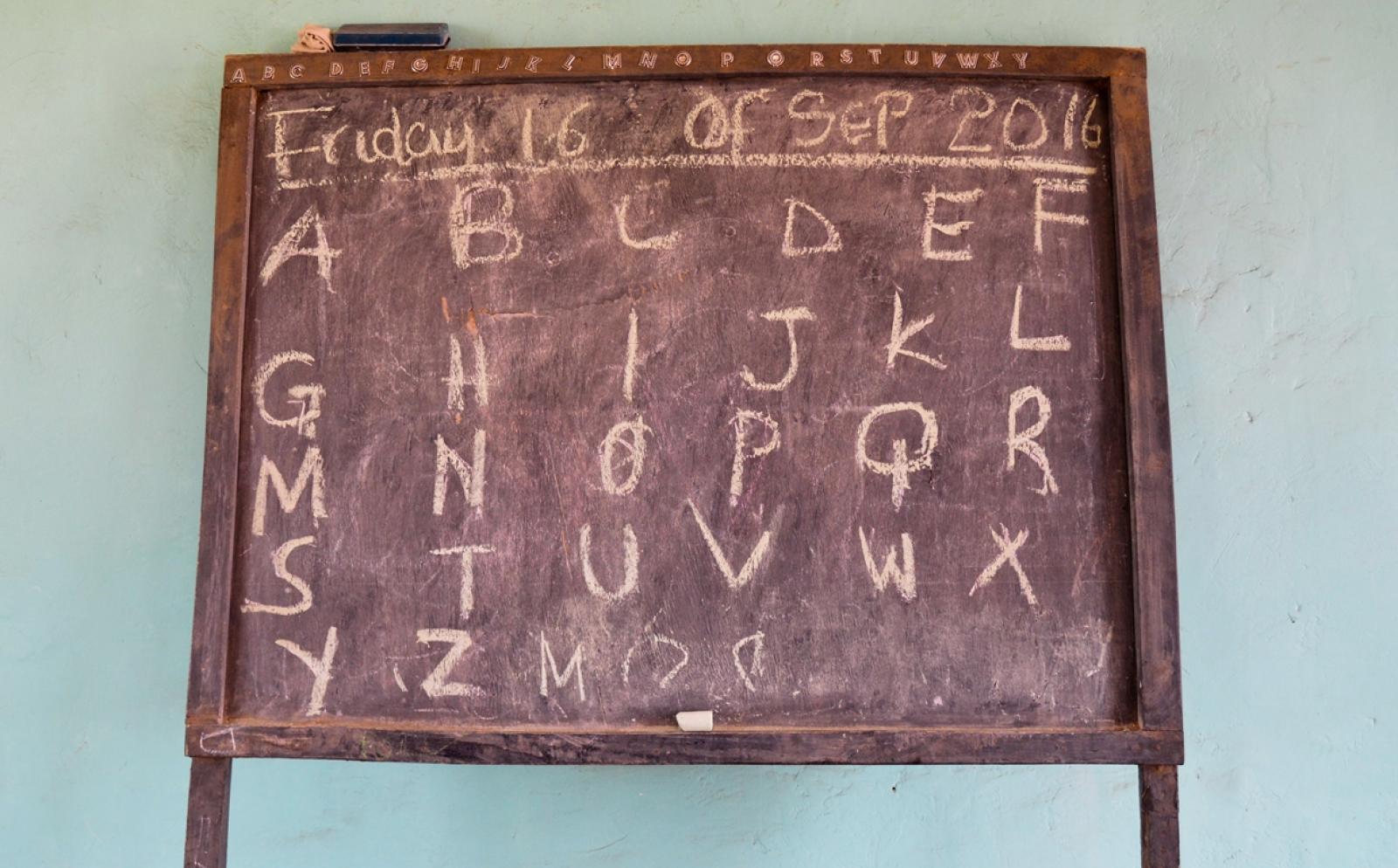 チョークで英語のアルファベットを黒板に書く